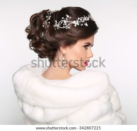 Elegant brunette woman in white fur coat. Wedding Hairstyle. Beautiful fashion bride girl model portrait. Luxury jewelry. Attractive young woman with brown hair. - stock photo