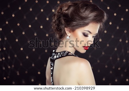 Elegant brunette woman lady with makeup and hairstyle. Fashion girl model over bokeh lights background - stock photo