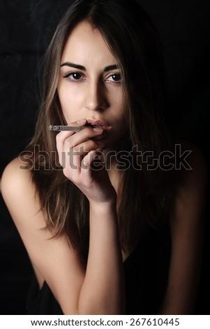 Elegant brunette woman smoking a cigarette black background - stock photo