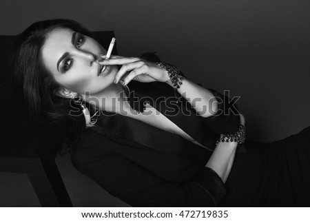 Elegant brunette woman smoking a cigarette on black background in studio