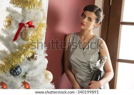 elegant brunette woman with silver dress near decorated christmas tree taking bottle of champagne for xmas or new year party