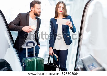 Elegant business couple with baggage getting up on the escalator to the departure area at the airport