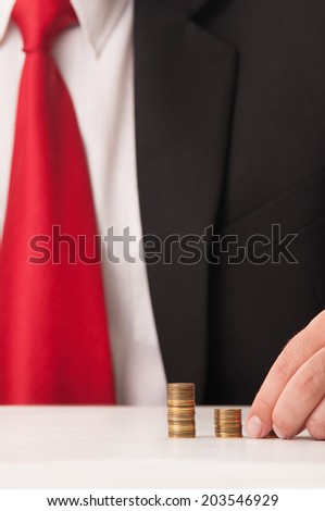 Elegant business man counting piles of coins and wearing black suit and red tie. Business success concept. - stock photo