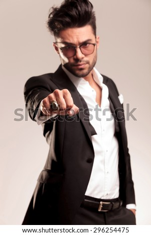 Elegant business man holding one hand in his pocket while showing his fist at the camera. He is wearing a big gold ring on his hand.