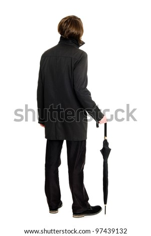 Elegant business man in a raincoat standing back and looking up. - stock photo