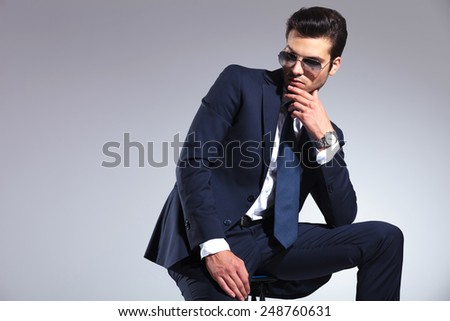 Elegant business man looking down to his side while holding one hand to his chin.