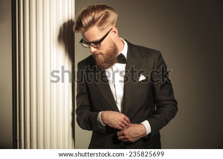 Elegant business man wearing a tuxedo posing near white column, looking down while closing his jackt. - stock photo