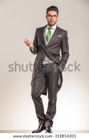 Elegant business man welcoming you while holding one hand in his pocket. - stock photo