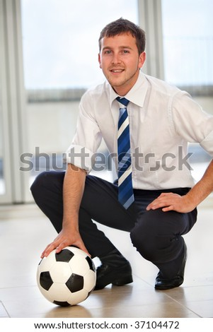 Elegant business man with a football smiling - stock photo