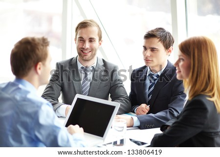 Elegant business partners listening to colleague at meeting - stock photo