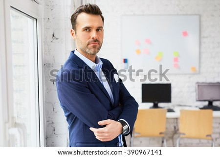 Elegant businessman at office looking at camera - stock photo