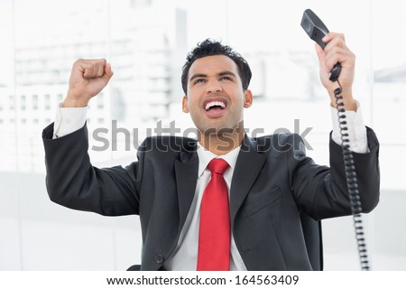 Elegant businessman cheering with telephone receiver at a bright office