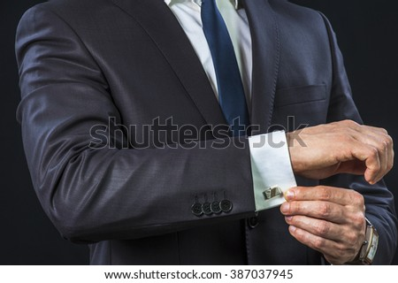 Elegant businessman correcting his cufflinks and sleeve. - stock photo