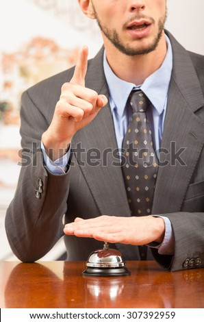 Elegant businessman customer ringing hotel bell in reception desk demanding attention close up - stock photo