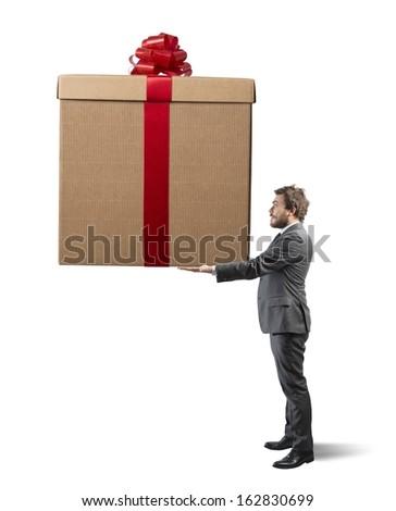 Elegant businessman holding a big Christmas present - stock photo