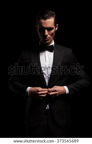 elegant businessman in black toxedo with bowtie posing in dark studio background while closing his jacket and looking at the camera