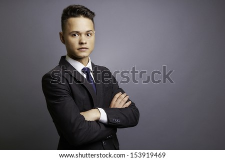 Elegant businessman in formal  suit and blue tie, arms crossed, leaning to the right, half body portrait, gray background, studio shoot.