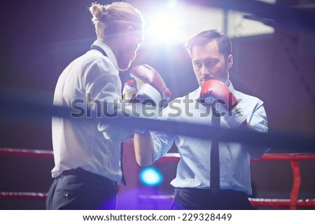 Elegant businessman in formalwear and boxing gloves looking at his rival before attack - stock photo