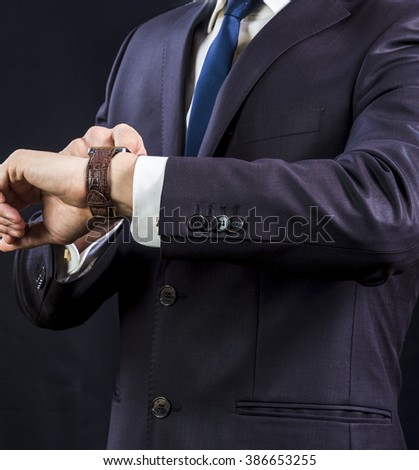 Elegant businessman in suit looking at his watch.  - stock photo