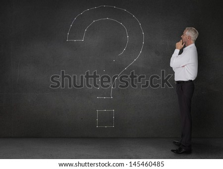 Elegant businessman looking at a giant question mark drawn on the wall - stock photo