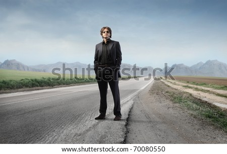 Elegant businessman on a city street - stock photo