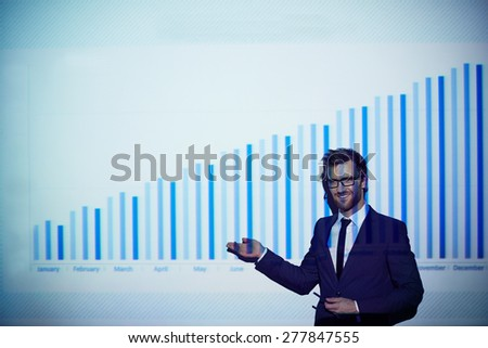 Elegant businessman pointing at chart on the wall