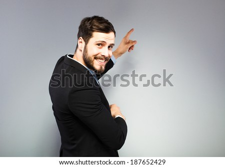 elegant businessman pointing the wall, on grey background - stock photo