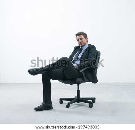 Elegant businessman sitting on an office chair in an empty room looking at camera. - stock photo