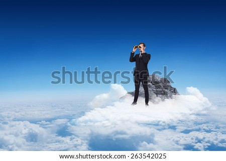 Elegant businessman standing and using binoculars against mountain peak through the clouds