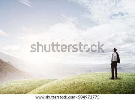 Elegant businessman standing on green hill and looking ahead