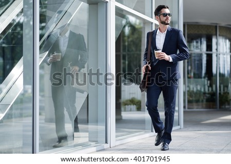 Elegant businessman with take-out coffee going to work - stock photo