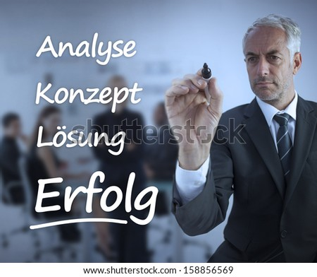 Elegant businessman writing marketing terms in german in front of a business team - stock photo
