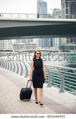 Elegant businesswoman carrying her luggage. - stock photo