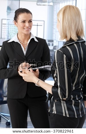 Elegant businesswoman discussing business at office. - stock photo