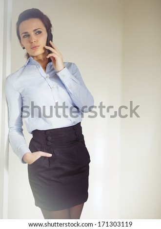 Elegant businesswoman dressed in skirt and shirt talking business on the phone. Caucasian woman in the 20s with modern smartphone. - stock photo