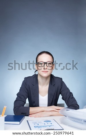 Elegant businesswoman looking at camera at her workplace - stock photo