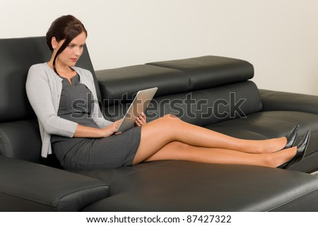 Elegant businesswoman on stylish leather sofa working touch tablet computer