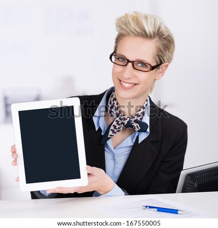 Elegant businesswoman or receptionist presenting a tablet-pc with a blank screen towards the viewer with a warm friendly smile - stock photo