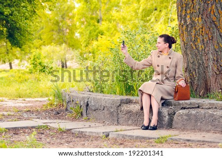 Elegant businesswoman sitting on a stone wall during a sunny spring day, and shooting a photo with her mobile phone