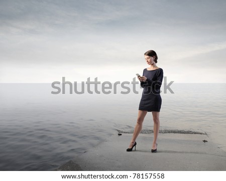 Elegant businesswoman standing on a beach using a mobile phone - stock photo