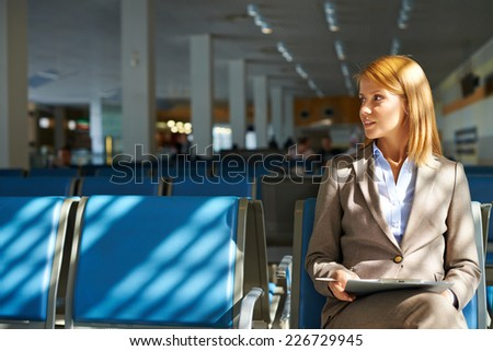 Elegant businesswoman with touchpad waiting for her flight in airport - stock photo