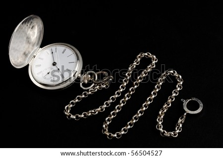Elegant carved silver pocket watch with chain isolated on black - stock photo