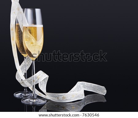 Elegant champagne glasses and a white christmas ribbon - stock photo