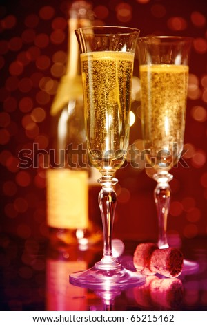 Elegant champagne glasses and bottle over holiday bokeh background, focus on first glass - stock photo