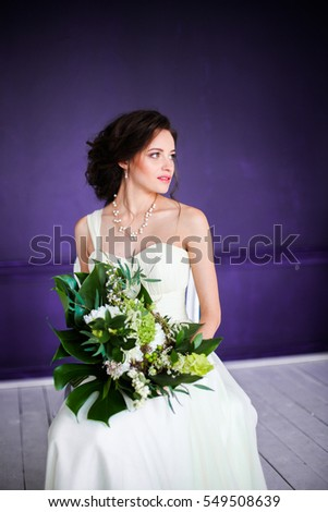 Elegant charming young brunette bride is posing indoors in a wedding dress with a big bouquet of flowers, in the minimalistic interior Waiting for groom.