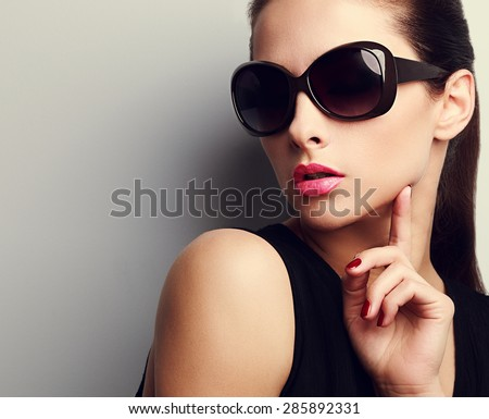 Elegant chic female model in fashion sunglasses touching hand the face. Closeup portrait