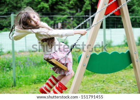 Elegant child girl in countrylike dress and red gumboots swinging in the park
