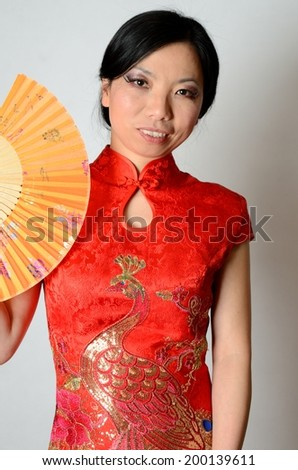 Elegant Chinese lady wearing traditional red dress. Pretty Asian female model holding fan in her hand.