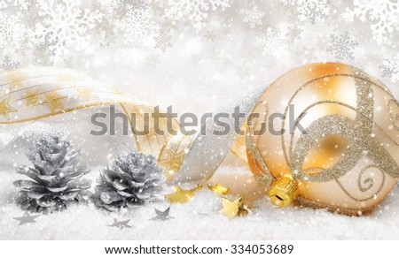 Elegant Christmas arrangement with a beautiful gold bauble, nice ribbons, silver cones, lots of snow and ornamental large snowflakes in the background - stock photo