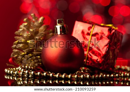 Elegant Christmas setting with simple red ornament, small present and golden pine cone in front of defocused red Christmas lights